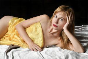 אישה שוכבת במיטה עם מגבת